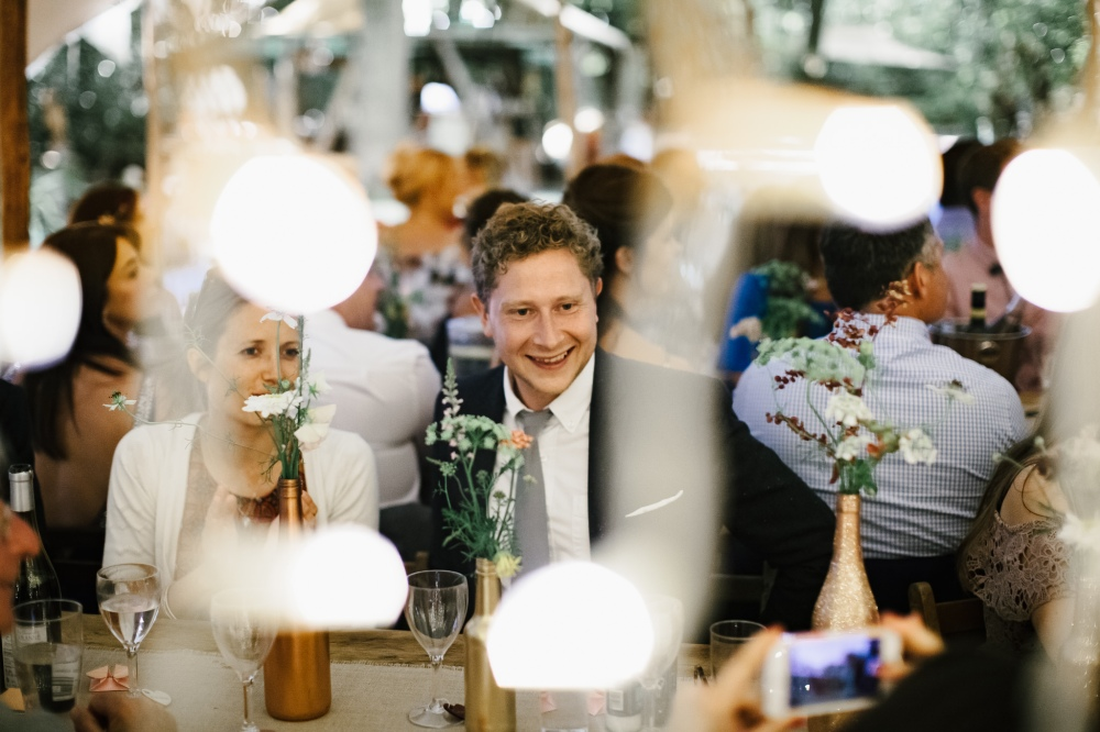 Real DIY Weddings, Table arrangements of Jam Jars and Bottles with loved ones gathered around