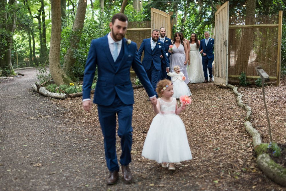 A Woodland Wedding, the bridal party walking down the pathway and through Narnia's doors, you walk into a beautiful clearing.