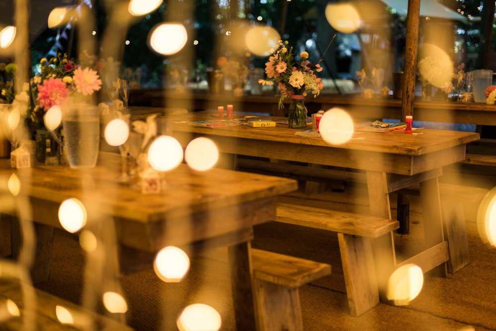Woodland Wedding rustic tables benches laid out with British Seasonal Flowers in Bottles and Jam Jars